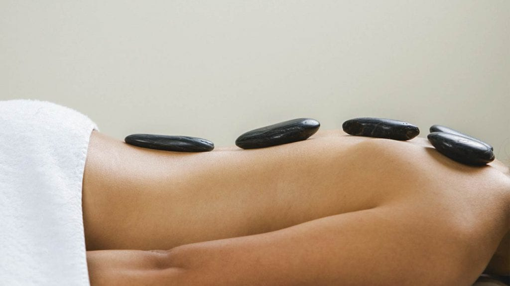 Hot stones on a woman's back as she lays on a massage table.